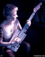 Woman playing cigar box guitar. Infrared light painted photograph.