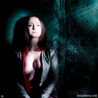 Woman with rough textured wall. Light painted photograph.