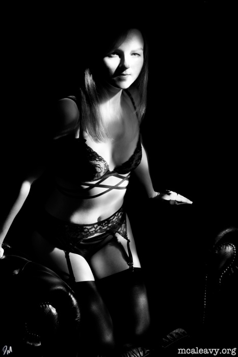 Shadowy woman with stockings and lingerie. Monochrome photograph.
