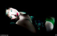 Woman reclining in a green corset. Light painting photograph.
