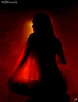 Woman in red translucent fabric. Light painted photograph.